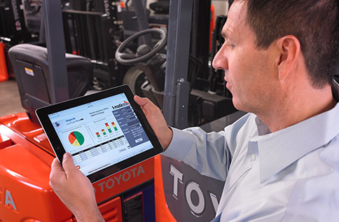 forklift fleet management program on a tablet is being reviewed next to a Toyota forklift